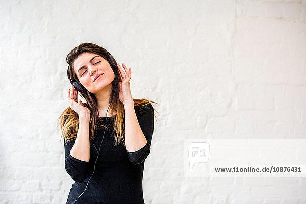 Hübsche junge Frau wiegt sich zu Kopfhörermusik vor weißer Wand