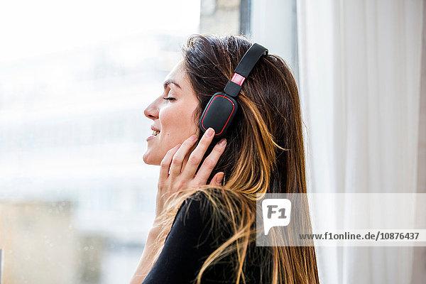 Junge Frau mit geschlossenen Augen  die vor dem Wohnungsfenster Kopfhörermusik hört