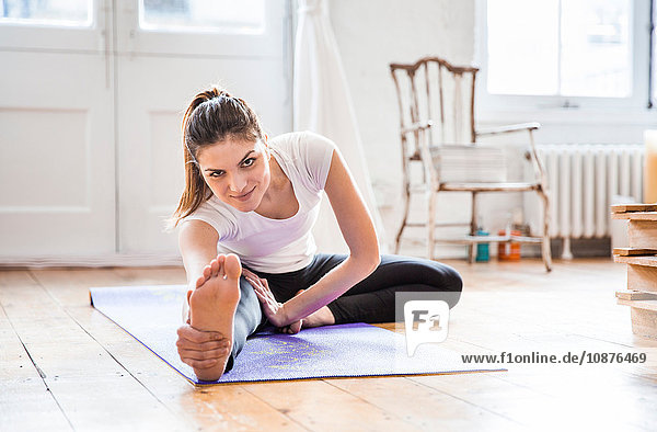 Young woman practicing yoga in apartment  touching toes