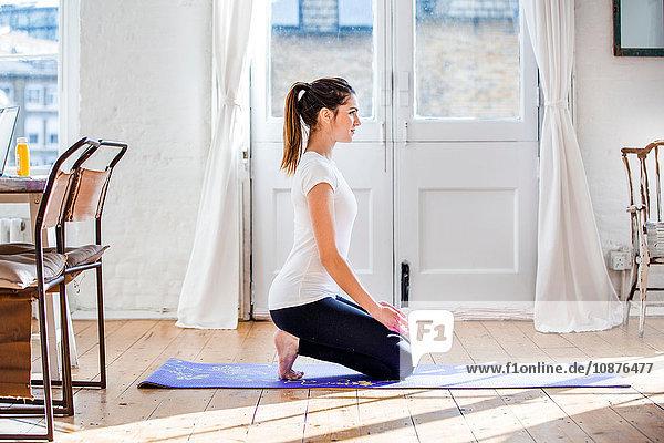 Junge Frau praktiziert Yoga in kniender Position in Wohnung