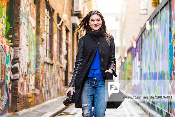 Portrait of stylish young woman with DSLR strolling along graffiti alley