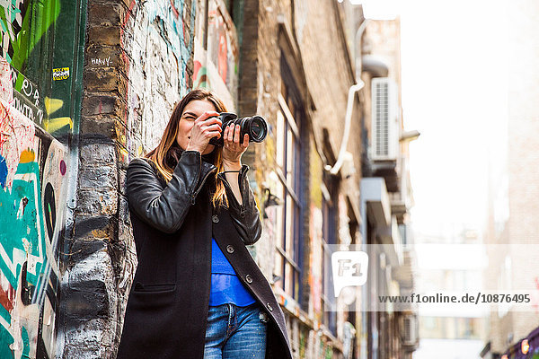 Young woman photographing in graffiti alley using DSLR
