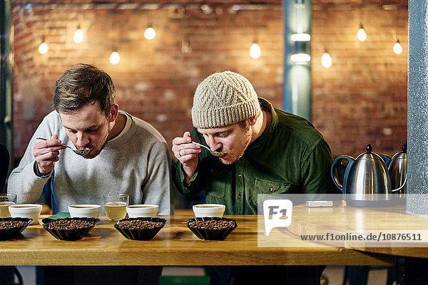 Coffee-Shop-Team schlürft Schalen mit Kaffee und Kaffeebohnen bei der Verkostung