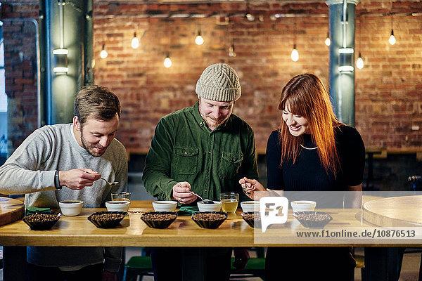 Team des Coffeeshops probiert Schalen mit Kaffee und Kaffeebohnen