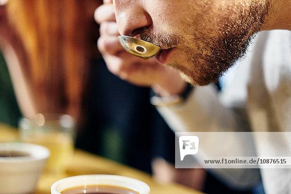 Nahaufnahme eines Mannes bei der Verkostung von Kaffeeschüsseln