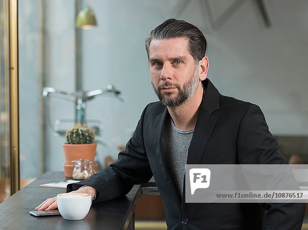 Portrait of cool businessman sitting at cafe window seat