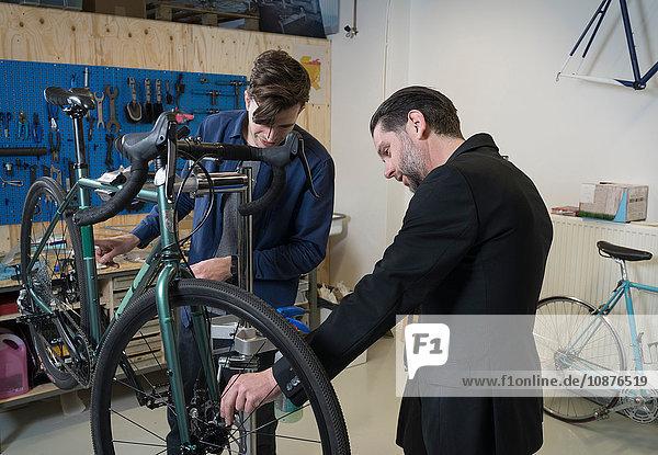 Zwei Männer überprüfen Fahrrad im Hipster-Rad-Reparatur-Café