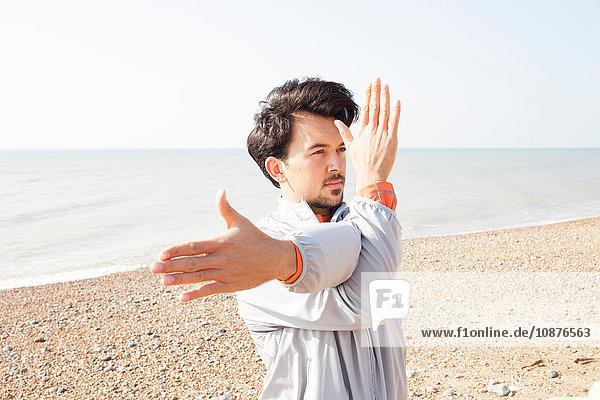 Young man warm up training  stretching arms on Brighton beach