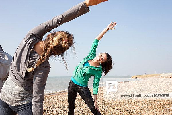 Zwei Frauen beim Aufwärmtraining  seitlich gebeugt am Strand von Brighton
