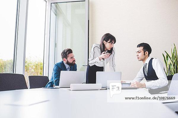 Geschäftsmänner und -frauen bei Besprechung am Vorstandstisch