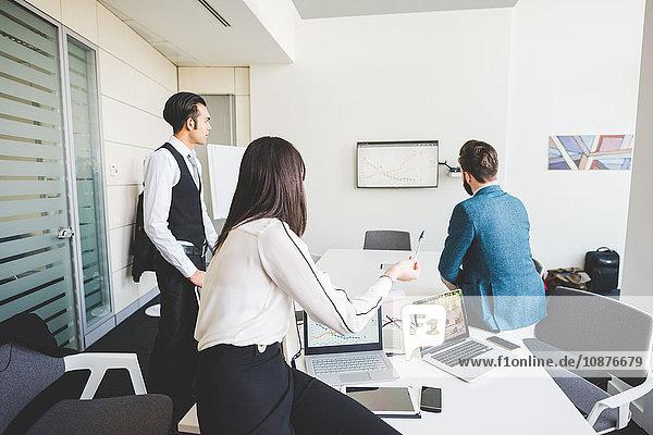 Geschäftsmänner und -frauen betrachten Diagramme in Büroteambesprechung