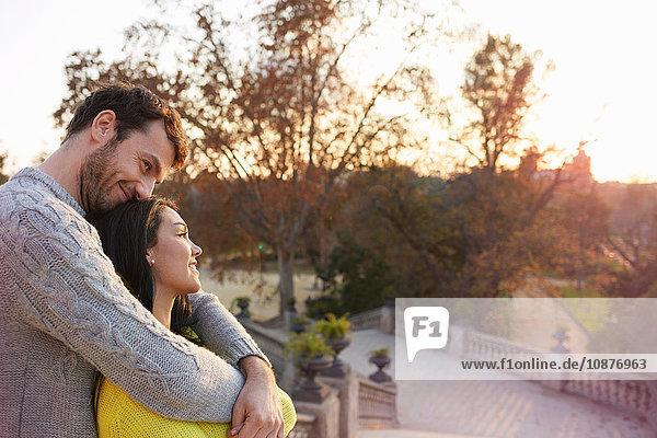 Paar im Park umarmt sich und genießt die Aussicht