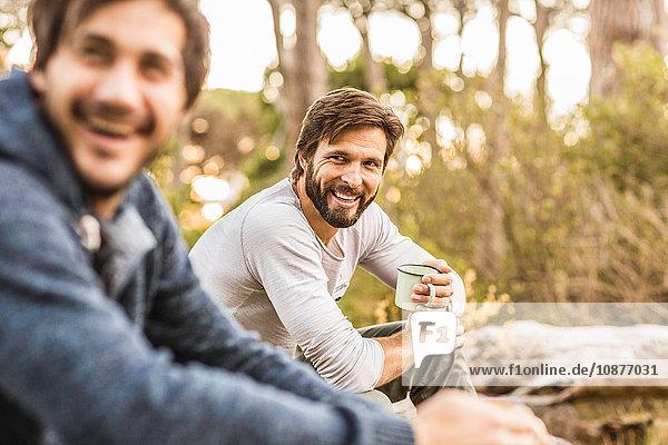 Zwei Männer trinken Kaffee  während sie im Wald sitzen  Deer Park  Kapstadt  Südafrika