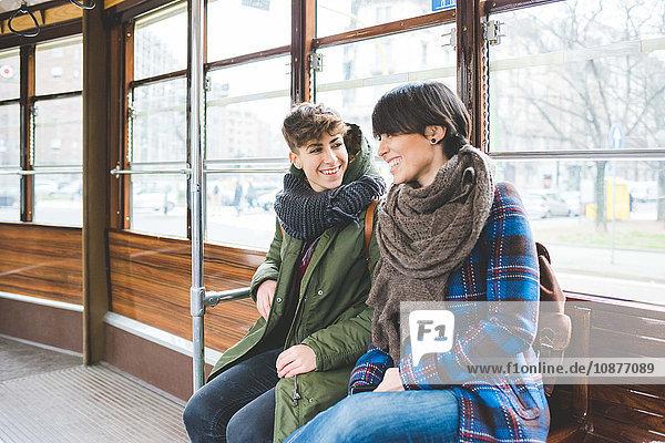 Zwei Schwestern auf der Seilbahn sitzend  lächelnd
