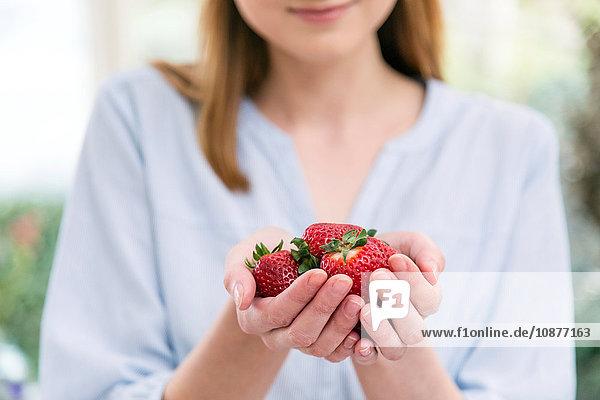 Frau mit schalenförmigen Händen  die Erdbeeren halten