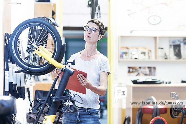 Woman in bicycle workshop holding clipboard checking bicycle