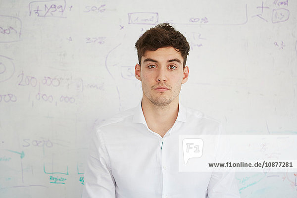 Man in front of white board looking at camera