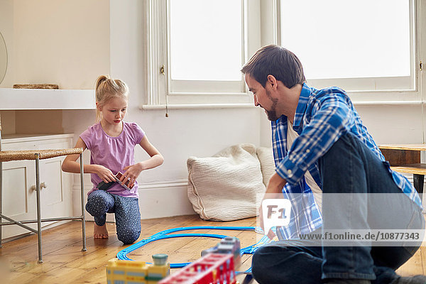 Father and daughter playing with toy train set