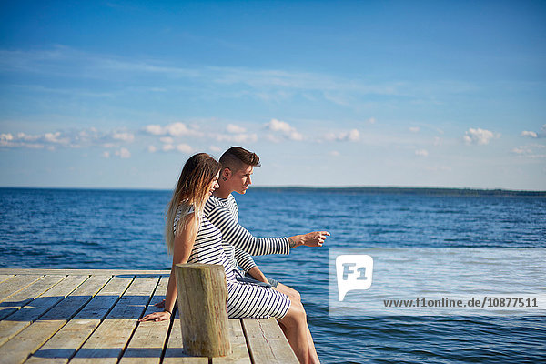Couple sitting on wooden pier  looking at view