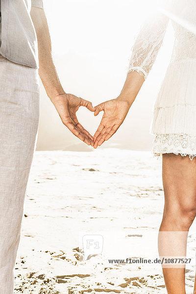 Ausschnittaufnahme eines Paares  das am sonnenbeschienenen Strand in Kapstadt  Südafrika  mit den Händen ein Herz formt