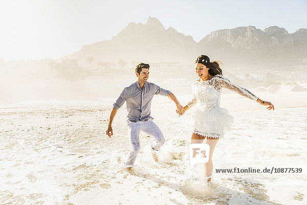 Paar rennt und planscht im sonnenbeschienenen Meer  Kapstadt  Südafrika
