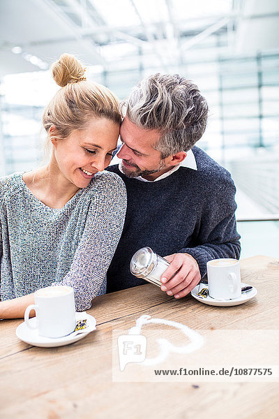Couple sitting together  drinking coffee  heart shape made from sugar on table in front of them