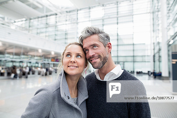 Ehepaar steht zusammen am Bahnhof und schaut auf