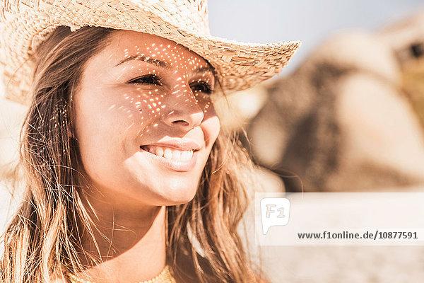 Nahaufnahme einer Frau mit Strohhut am sonnenbeschienenen Strand  Kapstadt  Südafrika