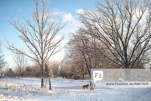 Two young girls with dog in snowy landscape