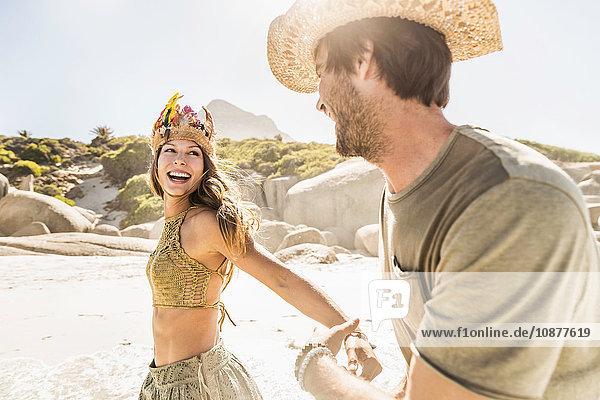 Mittelgroßes erwachsenes Paar mit Strohhut und Federkopfschmuck läuft am Strand  Kapstadt  Südafrika