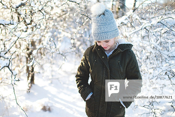 Young girl in snowy landscape  hands in pockets  looking down