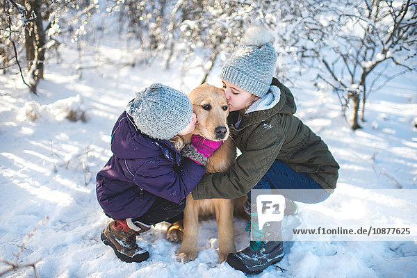 Two young girls  hugging dog  in snowy landscape