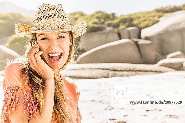 Porträt einer Frau mit Strohhut  die sich mit einem Smartphone am Strand unterhält  Kapstadt  Südafrika