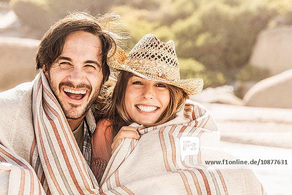Porträt eines Paares mittlerer Erwachsener in eine Decke gehüllt am Strand  Kapstadt  Südafrika