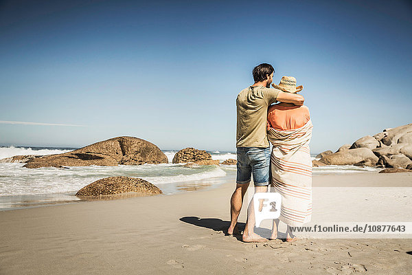 Rear view of couple wrapped in blanket looking out from beach  Cape Town  South Africa