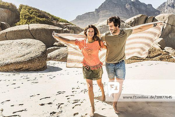 Paar  das eine am Strand laufende Decke hochhält  Kapstadt  Südafrika