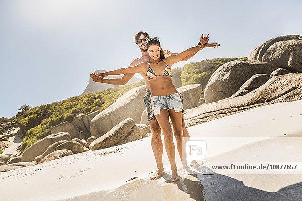 Paar in Badebekleidung mit offenen Armen am Strand  Kapstadt  Südafrika