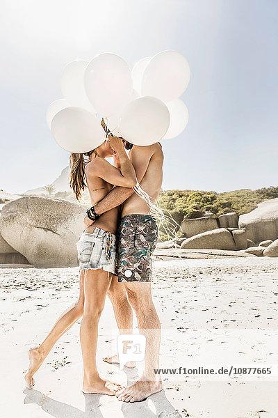 Paar hält einen Haufen Luftballons  die sich am Strand küssen  Kapstadt  Südafrika