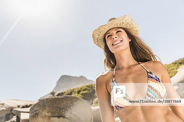 Niedrigwinkelansicht einer Frau mit Bikinioberteil und Strohhut am Strand  Kapstadt  Südafrika