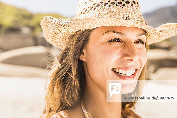 Headshot of woman wearing straw hat on beach  Cape Town  South Africa