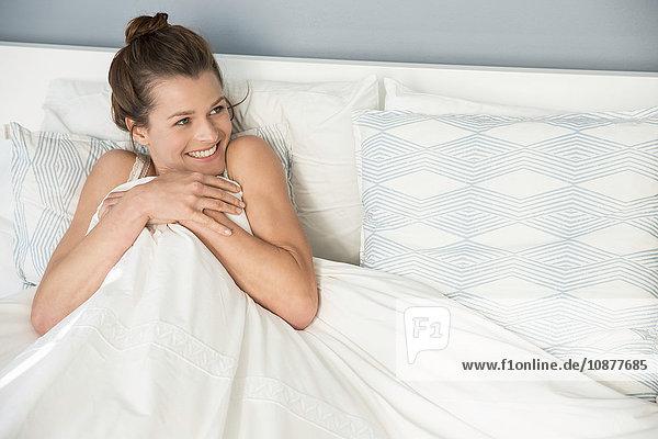 Junge Frau sitzt kichernd im Bett