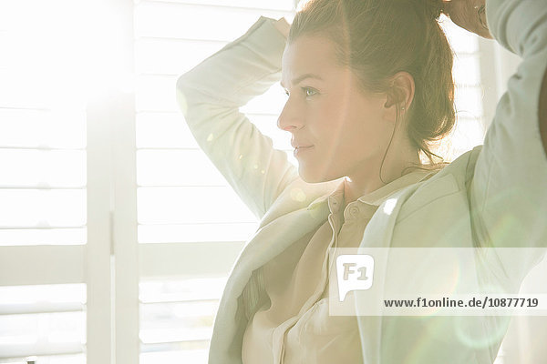 Young businesswoman styling hair in sunlit bedroom