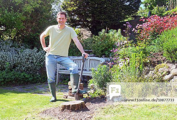 Mann im Garten hält Mistgabel und schaut lächelnd in die Kamera