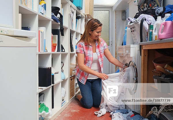Woman in utility room removing laundry from washing machine