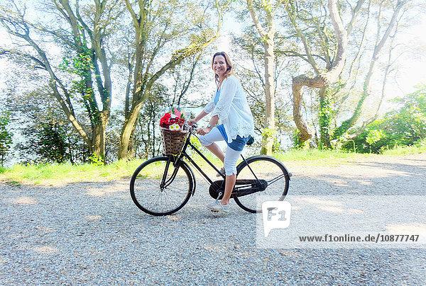 Frau auf Fahrrad schaut lächelnd in die Kamera