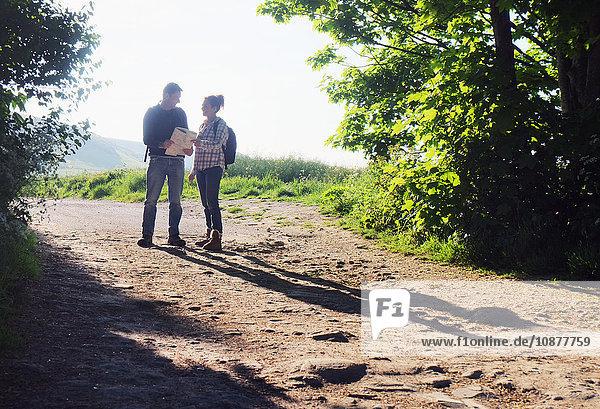 Paar wandert auf Feldwegen und liest Karte