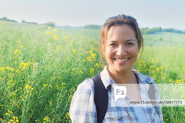 Porträt einer Frau im Rapsfeld  die lächelnd in die Kamera schaut