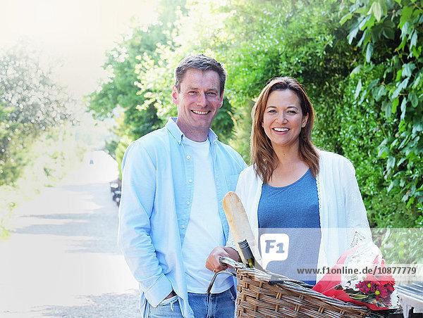 Paar mit Fahrrad schaut lächelnd in die Kamera