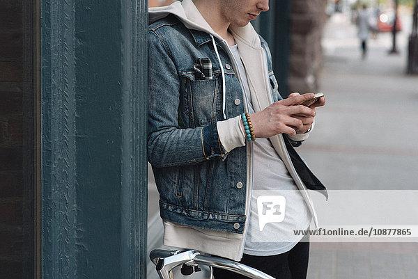 Junger Mann lehnt an Wand  benutzt Smartphone  Mittelteil