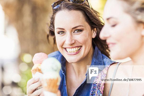Freunde halten Eistüten lächelnd in der Hand